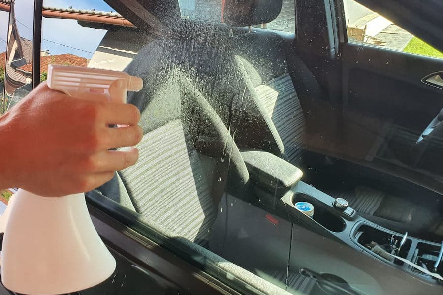 Cleaning car windows with alcohol.