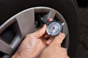 Checking tire pressure using gauge.