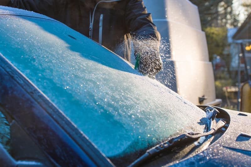 A man cleans frozen windshield. How to prevent windshield from freezing,