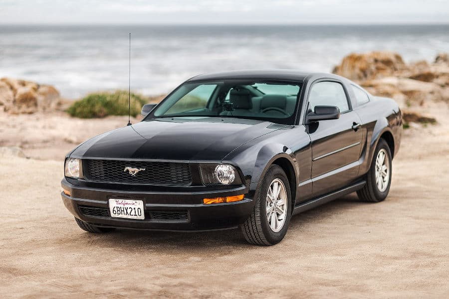Black car Mustang parked on the beach.