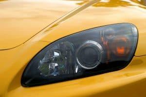 Xenon head light of a yellow sports car.