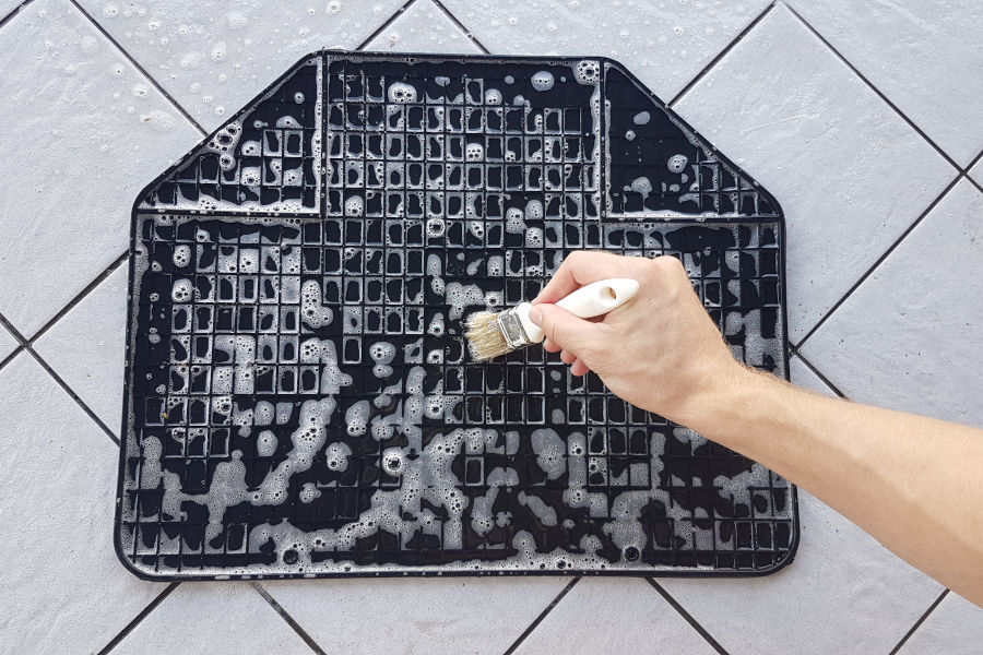 Using a brush for cleaning rubber car floor mats.