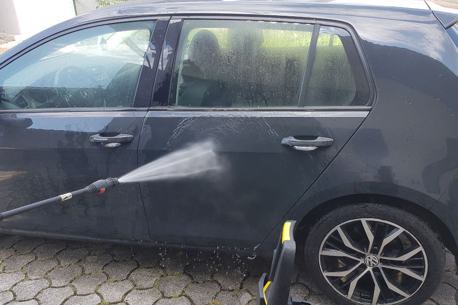 Using pressure washer to clean the car.