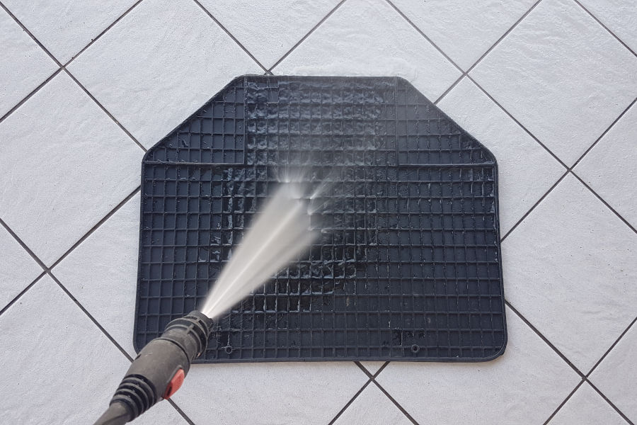 Washing car floor mats with a pressure washer.