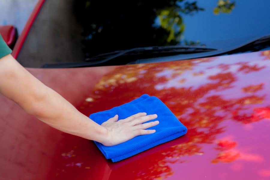 Wiping dust of a car with a microfiber cloth.