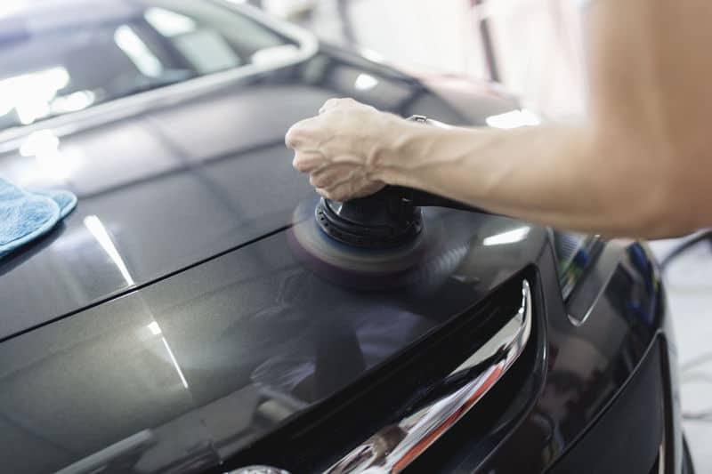 Using random orbital sander for car polishing.