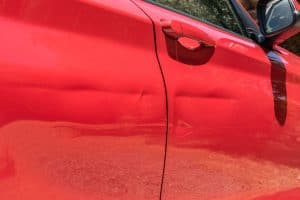 Dented red car door.